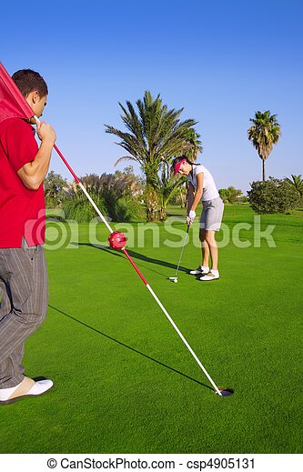 golf woman putting gol ball and man holds flag - csp4905131