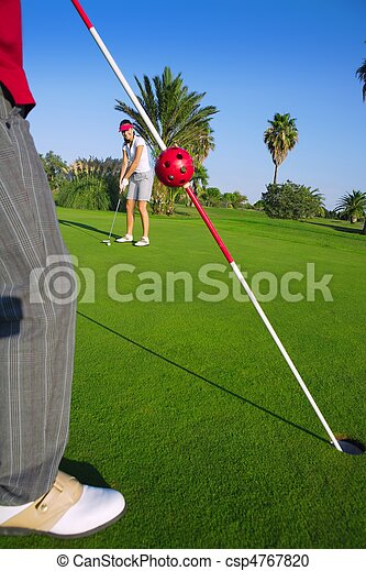 golf woman putting gol ball and man holds flag - csp4767820