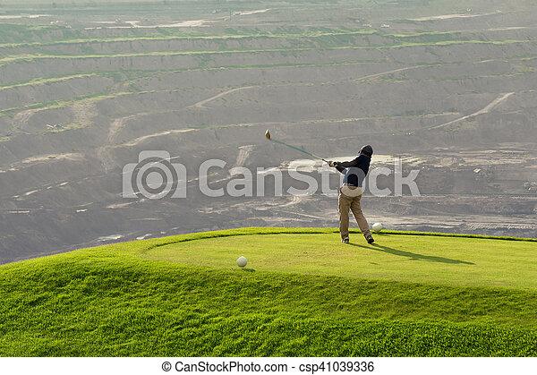 Golfer Hitting Ball with Club on Beatuiful Golf Course - csp41039336