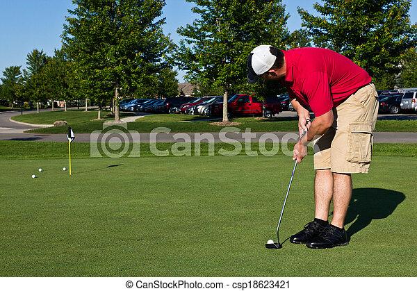 Golfer practicing putting golf balls - csp18623421