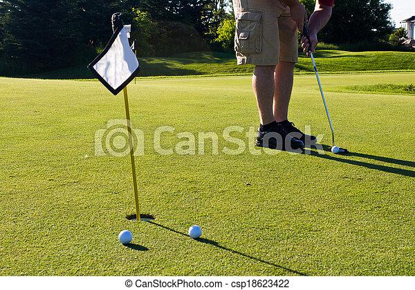 Golfer practicing putting golf balls - csp18623422