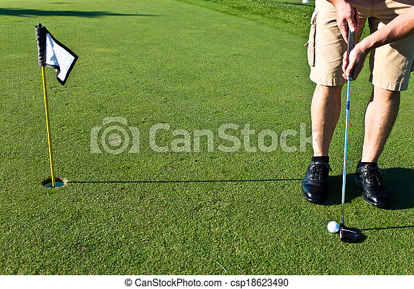 Golfer putting the golf ball - csp18623490