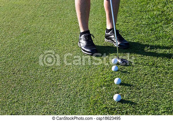 Golfer putting the golf ball - csp18623495