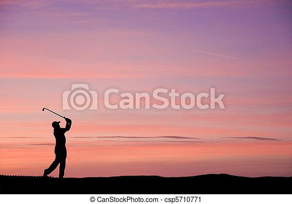 Golfer silhouette against stunning sunset sky - csp5710771