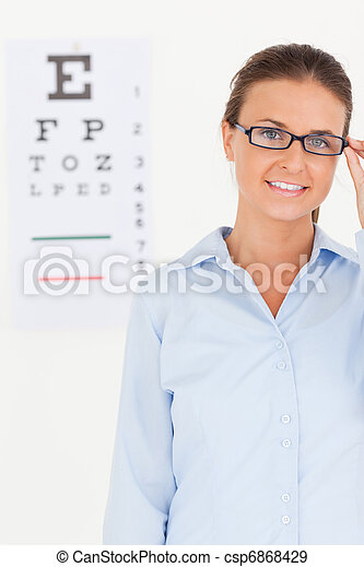 Good looking brunette eye specialist wearing glasses looking into the camera in her surgery - csp6868429