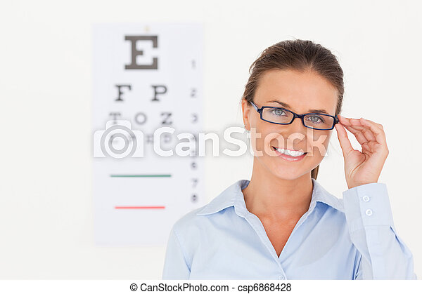 Good looking eye specialist wearing glasses looking into the camera in her surgery - csp6868428