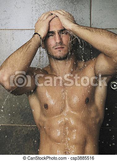 good looking man under man shower - csp3885516