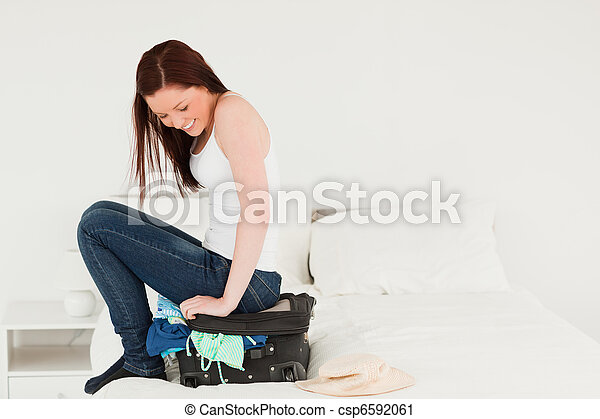 Good looking woman sitting on her suitcase - csp6592061