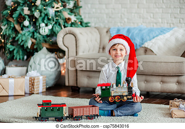 Good morning. Happy little boy with a gift, toy train, under the Christmas tree on New Year's morning. Time to fulfill wishes. - csp75843016