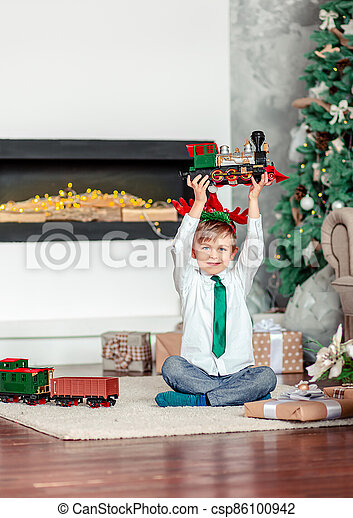 Good morning. Happy little boy with a gift, toy train, under the Christmas tree on New Year's morning. Time to fulfill wishes. - csp86100942