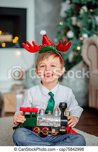 Good morning. Happy little boy with a gift, toy train, under the Christmas tree on New Year's morning. Time to fulfill wishes. - csp75842998