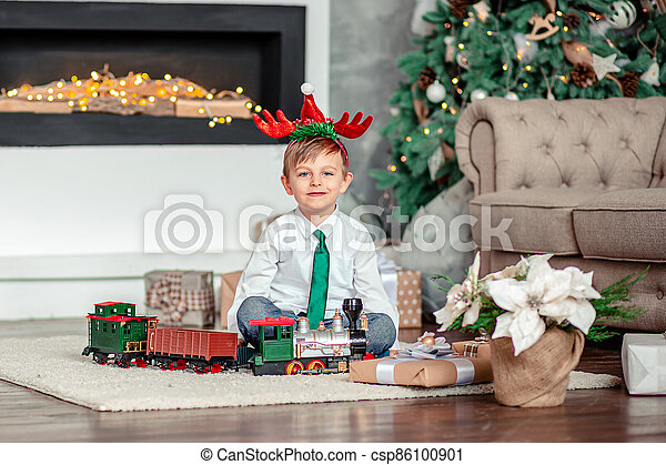 Good morning. Happy little boy with a gift, toy train, under the Christmas tree on New Year's morning. Time to fulfill wishes. - csp86100901