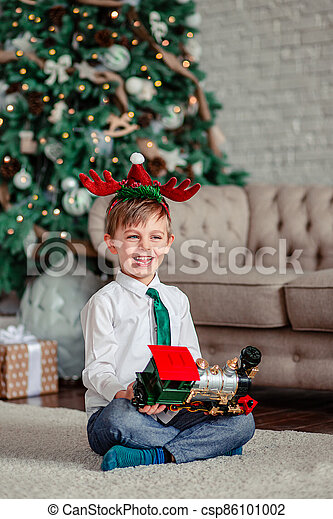 Good morning. Happy little boy with a gift, toy train, under the Christmas tree on New Year's morning. Time to fulfill wishes. - csp86101002