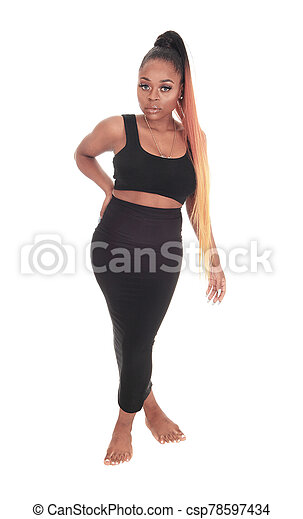 Gorgeous African woman standing in a black dress - csp78597434