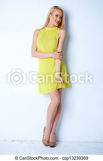Gorgeous blond woman posing in yellow dress - csp13239369