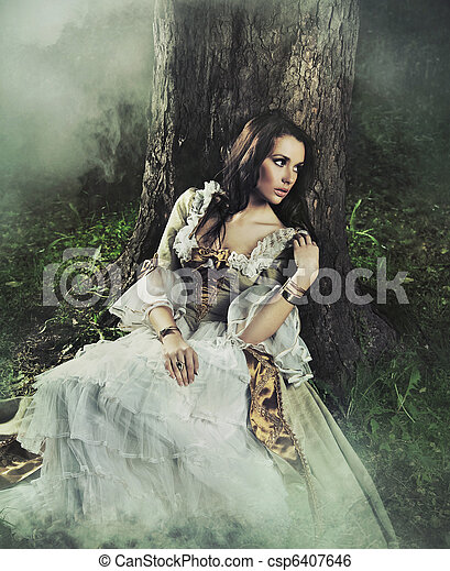 Gorgeous brunette beauty in a old-fashioned dress in a forest - csp6407646