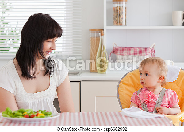Gorgeous brunette woman having a meal with her baby while sitting in the kitchen - csp6682932