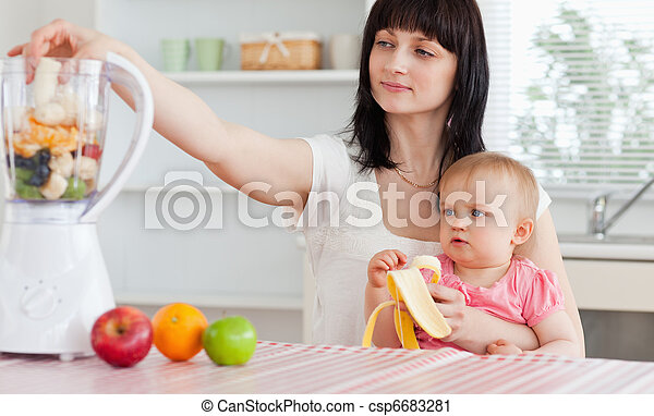 Gorgeous brunette woman putting vegetables in a mixer while holding her baby on her knees in the kitchen - csp6683281