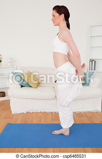 Gorgeous red-haired female stretching in the living room - csp6485531
