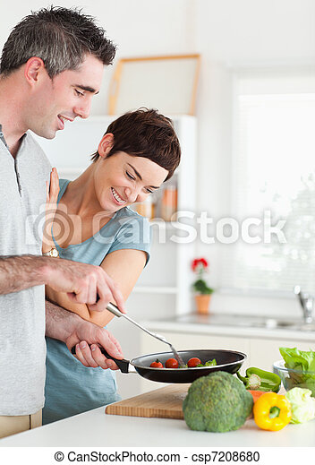 Gorgeous Woman looking into a pan her husband is holding - csp7208680