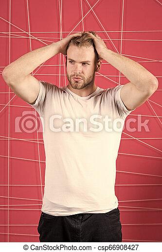 Un hombre con cara dura y estricta disfruta de la frescura del pelo, de fondo rosa. Un concepto de cuidado de pelo. Un tipo barbudo atractivo con peinado. Un hombre con barba o un tipo sin afeitar guapo y bien peinado tocando el pelo - csp66908427