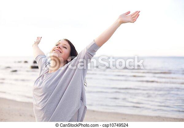 Mujer feliz estirando los brazos para disfrutar de la naturaleza - csp10749524