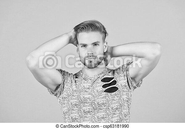 Un tipo barbudo atractivo con peinado. El hombre barbudo rostro estricto disfruta de la frescura del pelo, fondo gris. Un concepto de cuidado de pelo. Un hombre con barba sin afeitar guapo y bien peinado tocando el pelo - csp63181990