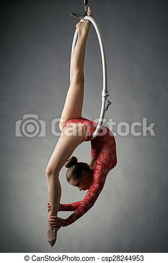 Graceful acrobat performs gymnastic trick on hoop - csp28244953