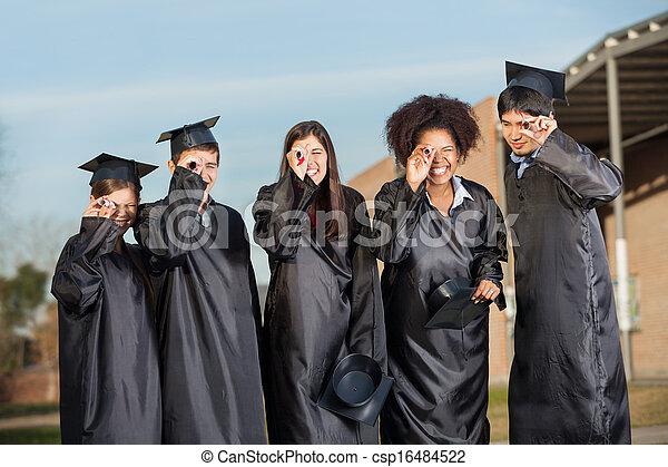 Graduate Students Looking Through Diplomas On Campus - csp16484522