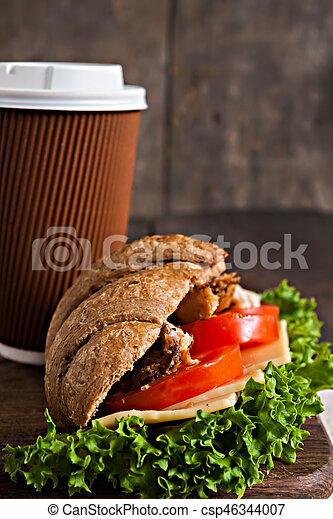 grain croissant sandwich and a cardboard cup of coffee on a dark background - csp46344007