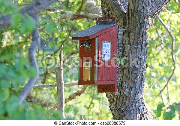 Gran teta sentada en la casa de los pájaros pintados - csp28388573