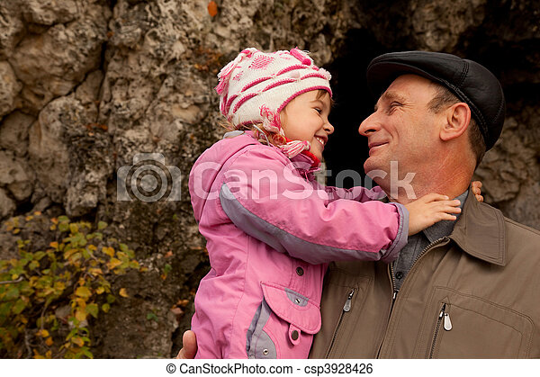 Grandfather hold granddaughter in his nahds near the stone wall - csp3928426