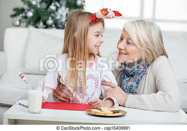 Grandmother And Girl With Cardpaper Looking At Each Other - csp16409991