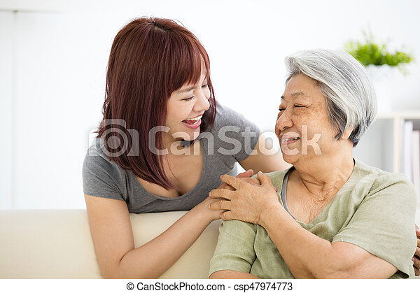 Grandmother and granddaughter. Young woman carefully takes care of old woman - csp47974773