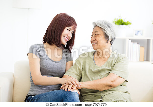 Grandmother and granddaughter. Young woman carefully takes care of old woman - csp47974779