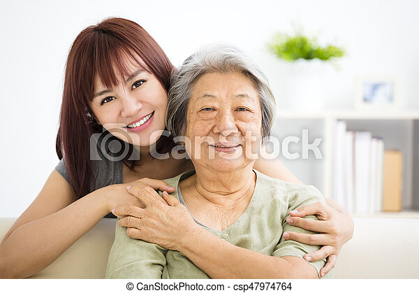 Grandmother and granddaughter. Young woman carefully takes care of old woman - csp47974764