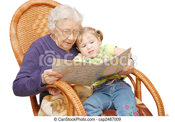 Grandmother reads to the granddaughter in an armchair - csp2487009