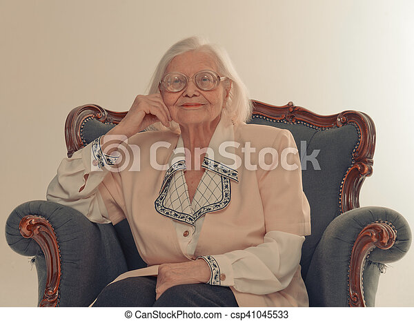 Grandmother sitting in an old chair. smiles.