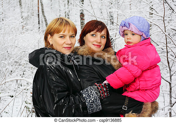 Grandmother, young mother and little daughter stand in woods in snow at winter - csp9136885