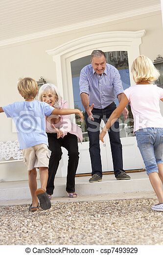 Grandparents Welcoming Grandchildren On Visit To Home - csp7493929