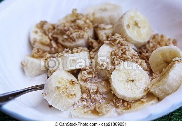 Granola, bananas, cream in a bowl - csp21309231