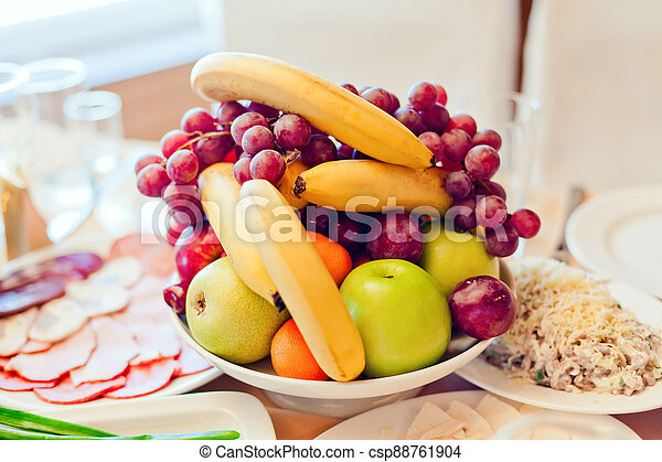 Grape, apples, pears, bananas and other fruits in a vase on a festive table - csp88761904