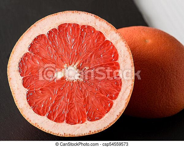 Grapefruit on black stone background on white wooden table - csp54559573