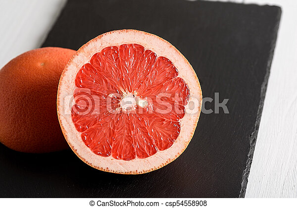 Grapefruit on black stone background on white wooden table - csp54558908