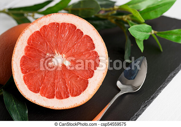 Grapefruit with spoon and leaves on black stone background on white wooden table - csp54559575