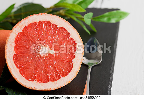 Grapefruit with spoon and leaves on black stone background on white wooden table - csp54558909