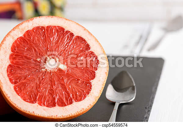 Grapefruit with spoon on black stone background on white wooden table - csp54559574