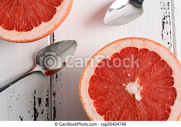 Grapefruit with spoon on white wooden background - csp55404746