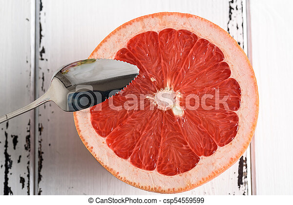 Grapefruit with spoon on white wooden background - csp54559599