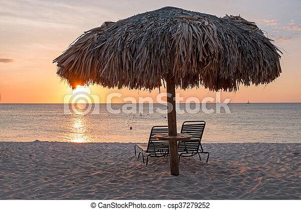 Grass umbrellas at the beach on Aruba island at sunset - csp37279252